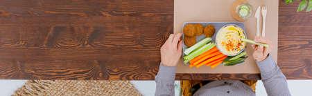 Rechthoekige plaat met falafel, groenten en hummus op rustieke lijst