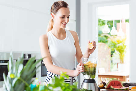 Smiling girl squeezing lemon juice into blender with water and sliced fruit while preparing smoothie