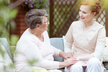 Elder woman sitting on garden couch while talking with red haired nurse in garden Stock Photo