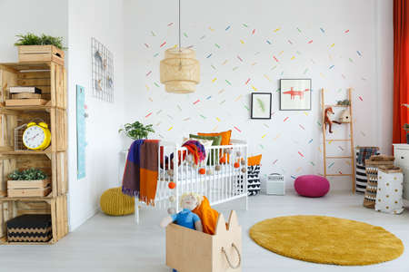 Toys in wooden box next to yellow carpet in scandi babys room with clock on shelf and white cradle Stock Photo