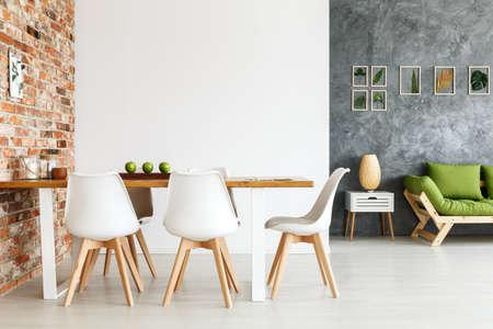 Design intérieur contemporain de la salle à manger avec table commune contre le mur de briques et salon ouvert avec des décorations de simples canap