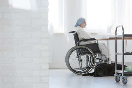 Disabled cancer patient sitting in a wheelchair at the hospital with her faithful black dog