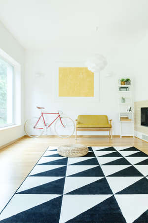Triangle carpet in spacious contrast color interior with gold painting on wall above yellow sofa and red bike