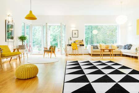 Yellow lamp above white round carpet next to yellow sofa in spacious apartment with triangle carpet Stock Photo