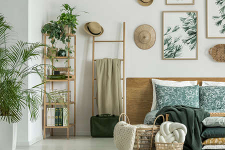Wooden ladder with coverlet and straw hat standing next to bed in bright room with plants Stock Photo