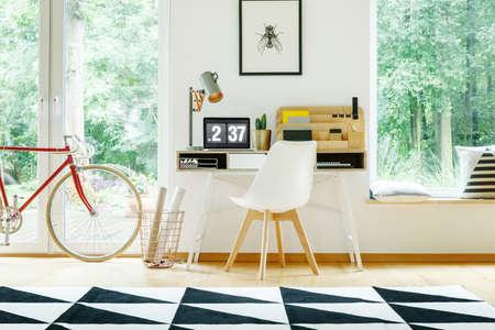 木製のオーガナイザーと表示のワークスペースでノート パソコン デスク ホワイトのモダンな椅子の近くの赤い自転車 写真素材
