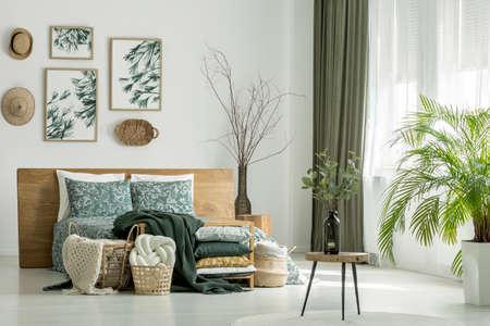 葉と小枝が絵画で白い寝室の小さなテーブルの上に花瓶立っての形をしたボトルに配置