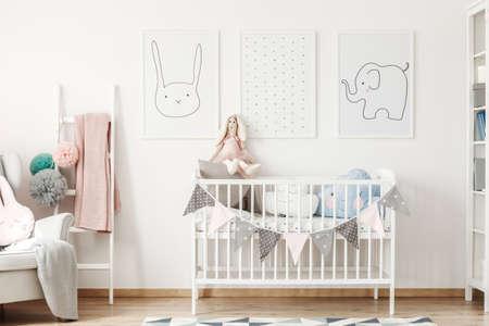 흰 벽 및 작은 사다리에 매달려 귀여운 동물 포스터 아래 서 어린이 크기 침대 스톡 콘텐츠
