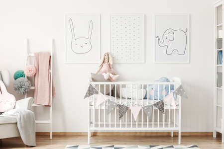 Child size bed standing under cute animal posters hanging on white wall and a small ladder