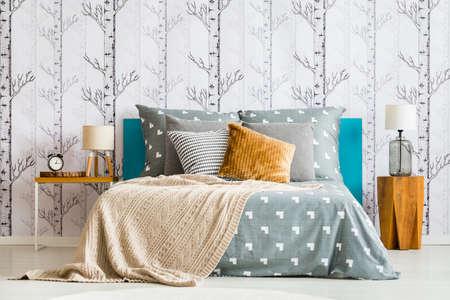 회색 침대보와 베이지 색 담요와 아늑한 침대의 근접 촬영, 숲 모티브가있는 흰색 벽지