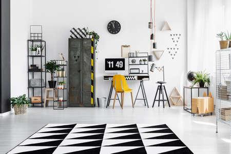 Ruime lichte industriële kamer met potplanten, een bureau, een kluisje en een lampenkap