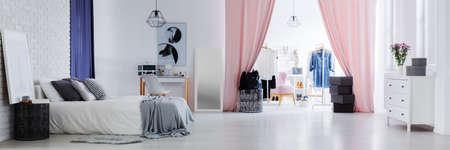 #88438030   Helles Stilvolles Schlafzimmer Für Frauen Mit Modischer  Kleidung In Der Geräumigen Umkleidekabine