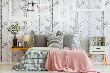 Dormitorio femenino interior con decoraciones inspiradas en el bosque y ropa de cama geométrica Foto de archivo