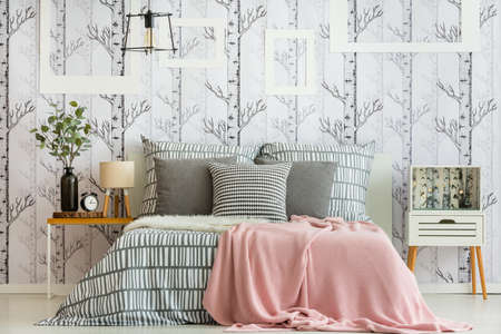 Vrouwelijk slaapkamerbinnenland met bos geïnspireerde decoratie en geometrisch beddegoed Stockfoto - 88438038