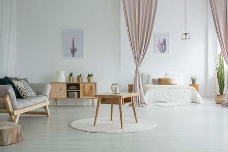 Spacious living room with wooden table on white carpet, rustic cupboard and grey sofa near open bedroom