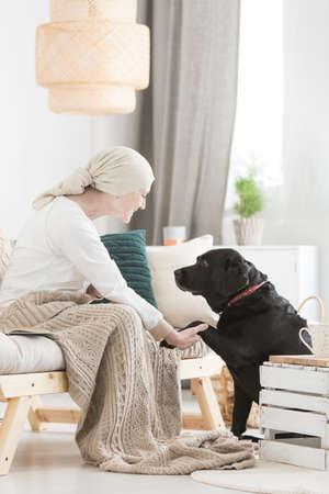 ペットを使ったセラピーの中に彼の足を保持することによって黒い犬との相互作用のがんの女性