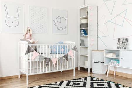 Grote boekenplank versierd met ballen van pastelkleurig katoen in het interieur van een kinderkamer