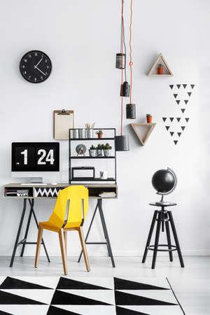 Lege die bol op zwarte kruk wordt geplaatst die zich naast bureau met computer en gele stoel bevinden