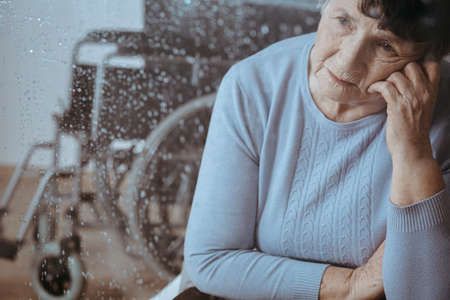 Incapacitado sênior mulher falta de família com cadeira de rodas em segundo plano