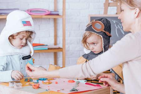 Děti v kostýmech, které vyrábějí plastelíny a sedí u stolu v předškolním zařízení