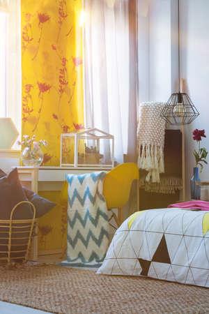 Yellow curtain in artistic bedroom with glasshouse on table and patterned blanket on chair