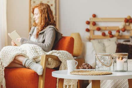 Kleine tafel met peperkoek en een thee, een kaars en een jonge dame die op de achtergrond een boek leest