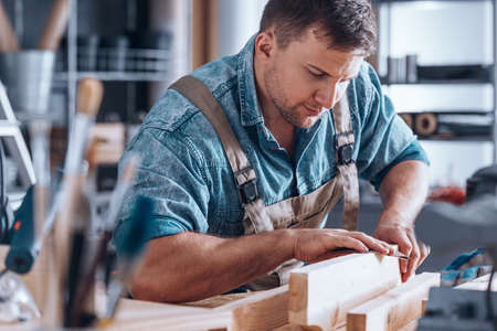 Close-up of handsome young carpenter wearing work clothes sanding a wooden plank in his workshop Фото со стока