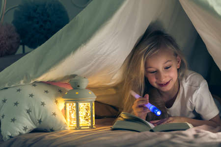 Young girl lying at night with a book