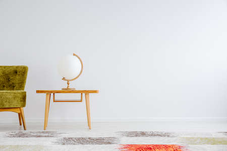 Wooden globe shaped lamp standing on small table in white room with copy space