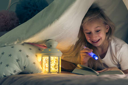 Young girl in bed reading a book with a flashlight