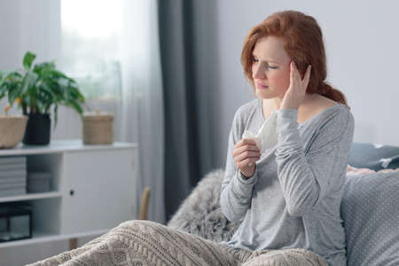 Sick young woman with a headache and fever sitting with a blanket on bed Stock Photo
