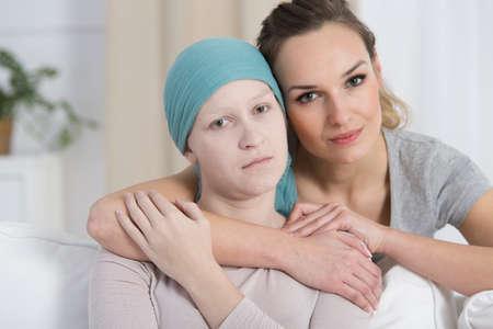 그냥 암 재발 진단을받은 슬픈 여자를 안고있는 희망찬 여자