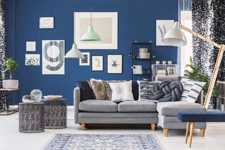 Designer metal tables near grey corner couch in spacious living room with gallery on blue wall Stok Fotoğraf