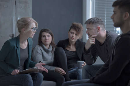 Support group meeting with female psychologist in a dark room Stock Photo