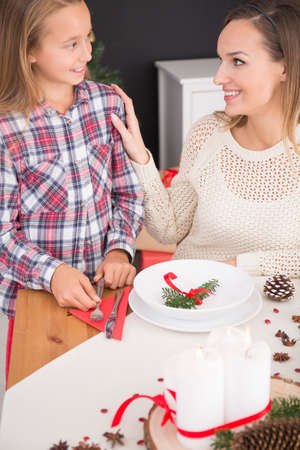 Young mother with her beautiful daughter prepare christmas table