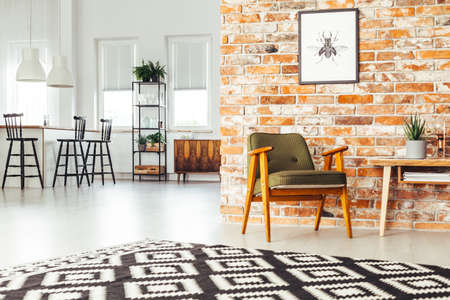 Poster on red brick wall above green retro chair next to wooden table in spacious living room with geometric carpet