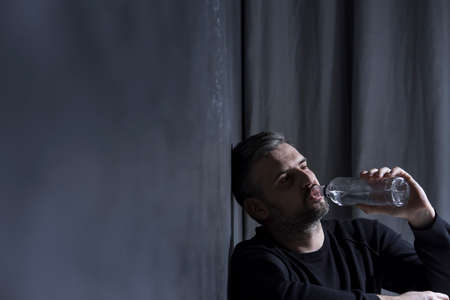 Unhappy man drinking alcohol while sitting alone in a dark room