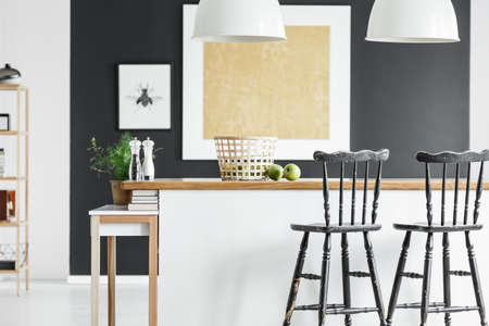 Basket and apples on wooden countertop and black bar stools in contrast color kitchen interior