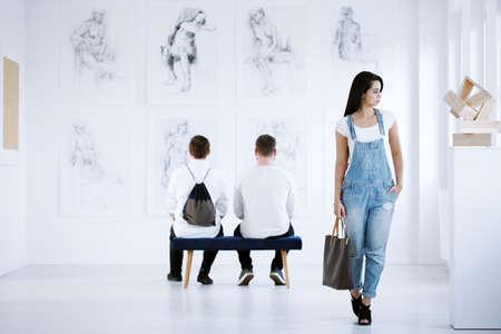 女性の行為を示すスタイリッシュな絵画を展示するアートギャラリー展