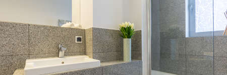 Modest modern bathroom with grey tiles and white sink