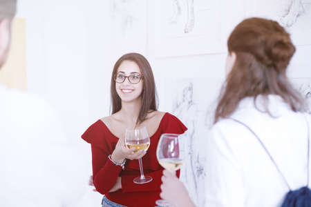 Young woman having a glass of wine at gallery opening while talking to other people
