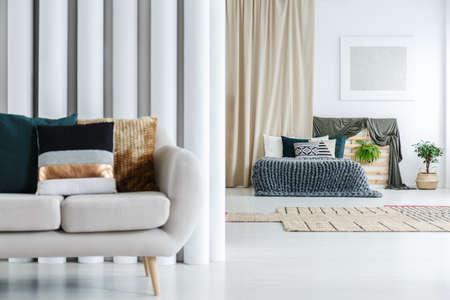 Cuscino a righe sul divano grigio in camera spaziosa con letto king-size contro tenda beige Archivio Fotografico