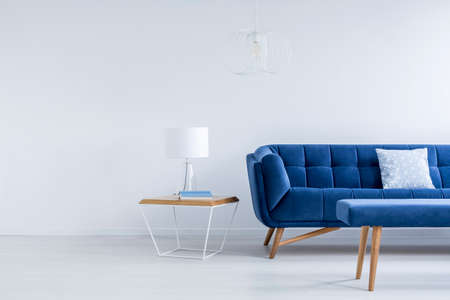 Kleine lamp en boek geplaatst op het nachtkastje staan naast royal blue sofa Stockfoto
