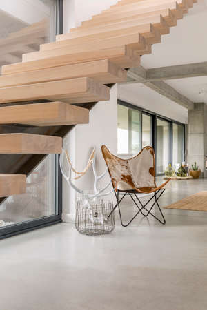 White antlers and handmade leather chair standing under wooden stairs in modern house