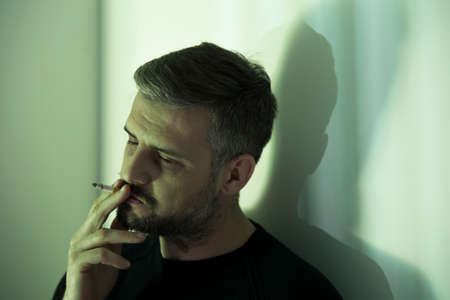 Nervous man with depression smoking a cigarette during lonely night at home Stock Photo