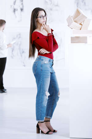 Girl in a red blouse contemplating a wooden piece of art in a museum