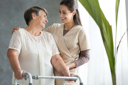 Smiling daughter supporting elderly mother using walker during meeting at home