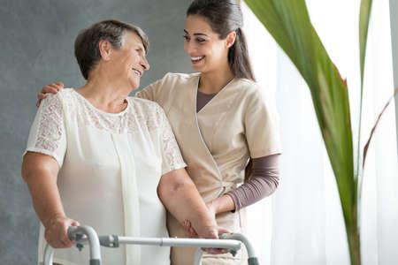 sourire fille aidant mère âgée en utilisant walker pendant la réunion à la maison Banque d'images