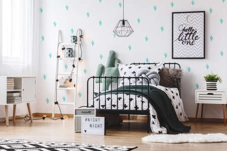 Groene deken op bed in heldere slaapkamer met poster op muur met schattige cactus behang