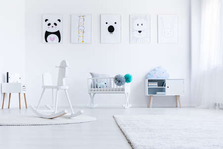 Low angle of rocking horse in bright babys bedroom interior with pastel pompons on cradle Stock Photo